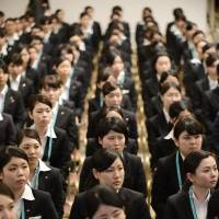 New employees at Seven & I Holdings Co. stand during an initiation ceremony in Tokyo in March 2013. | KYODO