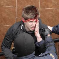A pro-European protester stands injured after clashes between his group and pro-Russian activists in the city of Kharkiv, in eastern Ukraine, on Sunday. | REUTERS