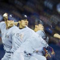 So it begins: Yankees starter Masahiro Tanaka pitches against the Blue Jays in the first inning on Friday in Toronto. Tanaka earned the win in his MLB debut. | AP
