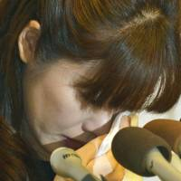 Haruko Obokata wipes away tears toward the end of a news conference in Osaka on Wednesday. | KYODO