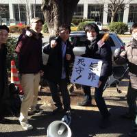 Victorious: Activists (left to right) Ryo Onda, Yosuke Oda, Yuichi Utsumi, Makoto Masui and Taku Arai gather around a placard reading 'Innocent: a desperately fought defense!' The  Tokyo High Court recently upheld their acquittal on charges under the Law for the Punishment of Acts of Violence in a case that became a rallying point for students across Japan. | COURTESY OF BUNKA RENMEI