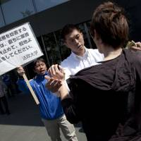 No entry: A student protester (right) is prevented from entering the Hosei University campus in Ichigaya, Tokyo, during a rally organized by the Bunka Renmei (Culture League) student group on Friday. The group is calling for disciplinary measures taken against students for their role in past protests to be repealed. | DAMON COULTER