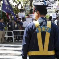 Ground zero: A policeman keeps watch at a student demo at Hosei University in Ichigaya, Tokyo, on Friday. | DAMON COULTER