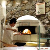 Eating Italian: A pizzaiolo works the furnace at Pizzeria Tonino. | ROBBIE SWINNERTON
