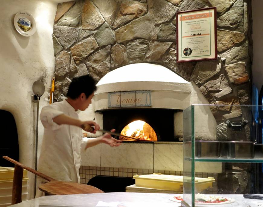 Eating Italian: A pizzaiolo works the furnace at Pizzeria Tonino.