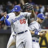 This is how we do it: Dodgers outfielders Yasiel Puig (66), Andre Ethier (right) and Carl Crawford celebrate after the final out of Los Angeles' 3-2 win over the Padres on Tuesday. | AP