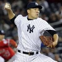 Under the bright lights: Yankees starter Masahiro Tanaka pitches against the Angels on Sunday at Yankee Stadium. New York rallied to defeat Los Angeles 3-2. | AP