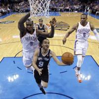Crowded out: San Antonio's Tony Parker goes to the basket in front of Oklahoma City's Serge Ibaka (left) and Russell Westbrook during the Thunder's 106-94 win over the Spurs on Thursday. | AP