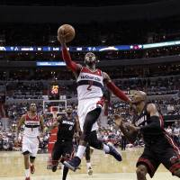 Open lane: Washington's John Wall goes up for a shot in front of Miami's Ray Allen in the second half on Monday. The Wizards ran past the Heat 114-93. | AP