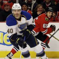 Even up: St. Louis' Maxim Lapierre moves the puck against Chicago in Game 4 on Wednesday night. The Blackhawks edged the Blues 4-3 in overtime and tie the series 2-2. | AP