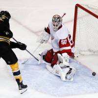 Point blank: Boston's Milan Lucic scores past Detroit goalie Jonas Gustavsson in the third period on Saturday night. | AP