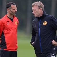 Changing of the guard: New Manchester United interim manager Ryan Giggs (left) talks to predecessor David Moyes during a training session last October. | AFP-JIJI