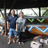 Hui Okinawa President Roy Hokama and former President Margaret Torigoe pose for a photo alongside the organization's sabani fishing canoe in Hilo. | HILLEL WRIGHT