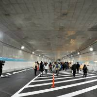 New frontier: People walk through the Tsukiji-Toranomon Tunnel on March 23. It officially opened to traffic six days later. | YOSHIAKI MIURA