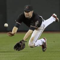 Almost: Arizona's A.J. Pollock is unable to catch a fly ball from Philadelphia's Ben Revere in the eighth inning on Saturday night. The Phillies beat the Diamondbacks 6-5. | AP