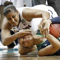 Up close and personal: Connecticut's Kaleena Mosqueda-Lewis (rear) fights for the ball with Notre Dame's Kayla McBride during the NCAA women's championship game on Tuesday. | AP