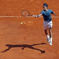 Casting a long shadow: Roger Federer plays a shot from the Czech Republic's Lukas Rosol in their third-round match at the Monte Carlo Masters on Thursday. Federer won 6-4, 6-1. | REUTERS