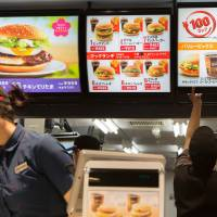 Still lovin' it?: An employee changes a board showing new prices at a McDonald's restaurant in Tokyo on Tuesday. While McDonald's Japan will raise prices of most menu items to reflect Japan's sales tax increase, the restaurant chain will cut the price of a hamburger to ¥100 from ¥120. | BLOOMBERG