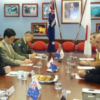 Defense Minister Itsunori Onodera (left) and his Australian counterpart, David Johnston, chat at the start of their meeting on joint equipment development in Perth, Australia, on Monday. | KYODO