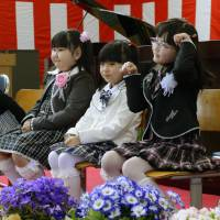 Four new first-graders attend the entrance ceremony at Furumachi Elementary School in the city of Tamura, Fukushima Prefecture, on Monday. The evacuation order for the Miyakoji district of Tamura was lifted on April 1 for the first time since the nuclear disaster began unfolding at the Fukushima No. 1 nuclear power plant in March 2011. | KYODO