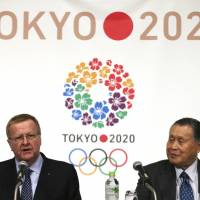 International Olympic Committee Vice President John Coates delivers a speech as Yoshiro Mori, president of the organizing committee for the 2020 Tokyo Olympic and Paralympic Games, listens at a press conference in Tokyo on Friday. | AP