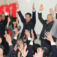Incumbent Kyoto Gov. Keiji Yamada (center) celebrates with supporters on Sunday night after winning re-election. | KYODO