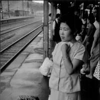 A work by award-winning photographer Shisei Kuwabara shows a woman waiting for a train at Minamata Station in Kumamoto Prefecture in August 1960 after leaving her son afflicted with Minamata disease behind. | SHISEI KUWABARA/KYODO