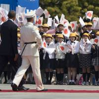 U.S. President Barack Obama walks past flag-waving children to inspect Japanese troops upon arriving for the welcoming ceremony at the Imperial Palace in Tokyo on Thursday. Later in the day, he places a prayer tablet at Meiji Shrine in Tokyo. | AP