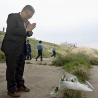 Koriyama Mayor Masato Shinagawa prays Thursday at the spot along the Abukuma River in Koriyama, Fukushima Prefecture, where a 6-year-old boy died the previous day attempting to save a 3-year-old girl who had fallen into the water. | KYODO