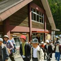Hikers crowd a trail Friday in the Osugidani Valley of Mie Prefecture after it reopened to the public for the first time in 10 years after being ravaged by a typhoon. | KYODO