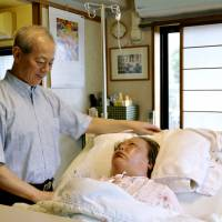By her side: An elderly man cares for his wife, who is afflicted with Alzheimer's disease. A predicted rise in Alzheimer's is likely to hit Japan's social-welfare system hard. | KYODO
