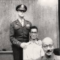 Slap happy: Shumei Okawa (center) is restrained  after slapping former Prime Minister Hideki Tojo (front) on the head on May 3, 1946, at the International Military Tribunal for the Far East. | www.britishpathe.com
