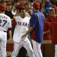 It's finally over: Robinson Chirinos (left) is congratulated by teammate Colby Lewis after his walk-off single against the Astros. | AP
