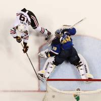 Go sing the blues: The Blackhawks' Jonathan Toews scores the winner past Blues goalie Ryan Miller during Game 5 on Friday in St. Louis. | AP
