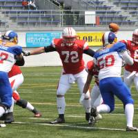 Perfect performance: Japan starting quarterback Shun Sugawara throws a pass while Philippines defenders Marc Anthony Patiag (59) and Juan Paolo Suarez (97) give pressure during the first quarter of the Asian qualifier for the 2015 IFAF World Championship. Sugawara completed 4 of 4 passes, including two touchdowns, in Japan's 86-0 triumph on Saturday. | HIROSHI IKEZAWA