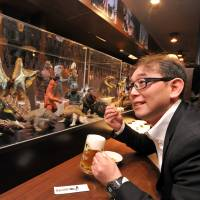 A man looks at a display case filled with 'kaiju' (monsters) near his table while relaxing with a beer at Kaiju Sakaba in Kawasaki. | YOSHIAKI MIURA