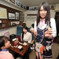 A waitress holds up a ticket punch and a fake train ticket as patrons wait to be served at Tetsudo-Izakaya Little TGV in Tokyo's Akihabara district. | YOSHIAKI MIURA