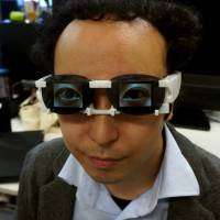 This combo picture released by University of Tsukuba assistant professor Hirotaka Osawa on Saturday shows the AgencyGlass. Developed by Osawa, its OLED screens display emotional expressions with the wearer's digital eyeball images.   AFP PHOTO/UNIVERSITY OF TSUKUBA/HIROTAKA OSAWA
