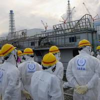 Members of the International Atomic Energy Agency inspect the crippled Fukushima No. 1 nuclear power plant during their review mission on the plant's decommissioning process on Nov. 27. | TOKYO ELECTRIC POWER CO./AFP-JIJI