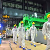 Members of the International Atomic Energy Agency's review mission inspect the crippled Fukushima No. 1 nuclear power plant on Nov. 27. | IAEA/AFP-JIJI
