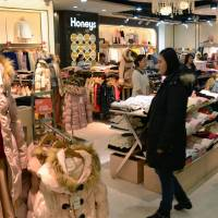 Customers browse at an outlet of Fukushima-based clothing chain Honeys Co. in Shanghai in January. | KYODO