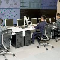 Members of the Self-Defense Forces cyberspace defense unit monitor computer systems in their cyberoperations center in Tokyo on March 24, two days before its launch. | DEFENSE MINISTRY/KYODO
