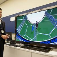 Hiroshi Sanko, a research engineer at KDDI R&D's Ultra-Realistic Communications Laboratory, demonstrates a video made with free-viewpoint imaging technology to show digitally replicated viewpoints at the lab in Fujimino, Saitama Prefecture, on March 25. | KAZUAKI NAGATA