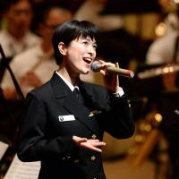 Petty Officer 3rd Class Yukari Miyake, 27, the sole vocalist of the Maritime Self-Defense Force Band, sings during a rehearsal for a concert in Matsudo, Chiba Prefecture, on Dec. 6, 2013. | AFP-JIJI/MARITIME SELF-DEFENSE FORCE