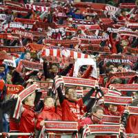 Urawa Reds fans celebrate the club's victory against Vegalta Sendai by raising scarves in support of the team at Saitama Stadium on April 6. | KYODO