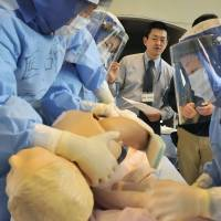Physician Hironobu Tokunaga (rear, center) teaches medical staff at Ishikawa Prefectural Central Hospital in Kanazawa how to treat people for radiation exposure in a practice session on Feb. 9. | KYODO