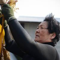 Professional diver Machiyo Yamashita dries 'wakame' (seaweed) she gathered off Shima, Mie Prefecture, last month. | BLOOMBERG