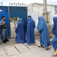 Afghan women enter a polling station in Jalalabad on Saturday to vote during the country's presidential election. | AP