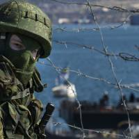 A Russian soldier guards a pier where two Ukrainian naval ships were moored in Sevastopol, Ukraine, on March 5 as Russian troops seized control of much of the peninsula in the Black Sea. | AP