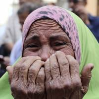 The mother of an accused supporter of ousted Islamist President Mohammed Morsi reacts in front of a courthouse in Minya, Egypt, after hearing that more than 680 Islamists were sentenced to death Monday. | REUTERS